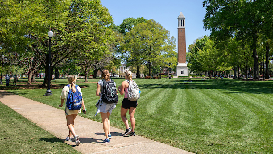 Students walking on quad with Denny Chimes in the background